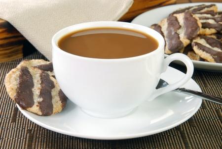 Een kopje koffie met room en havermout koekjes met fudge strepen