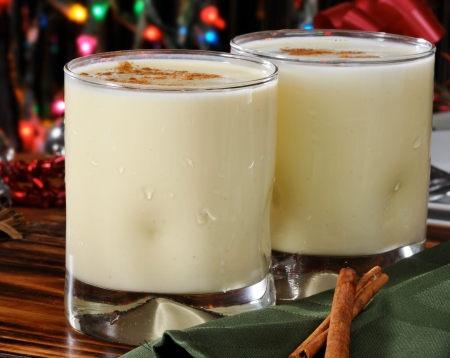 Two glasses of eggnog with cinnamon sticks near the Christmas tree