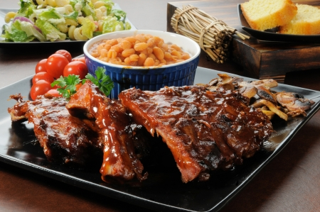 pork ribs: Racks of barbecue ribs drenched in sauce wiht salad and cornbread