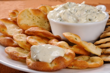 Close up of a chive and garlic pita crackers with spinach dip - shallow DOF focus on front cracker with dip