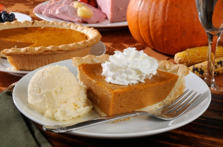 A slie of pumpkin pie with ice cream and a Thanksgiving dinner in the background