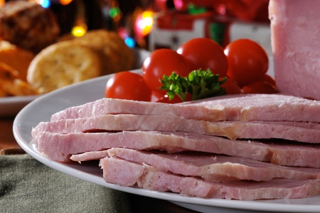 A Christmas buffet with sliced ham, crackers, cheese, tomatoes photo