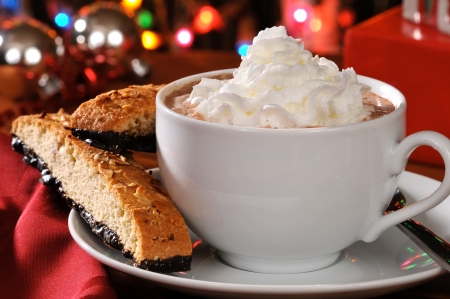 A cup of cappuccino or hot chocolate with almond chocolate biscotti in front of the Christmas tree