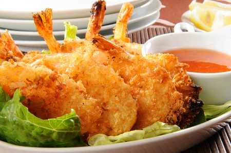 coconut: A plate of coconut shrimp with sauce
