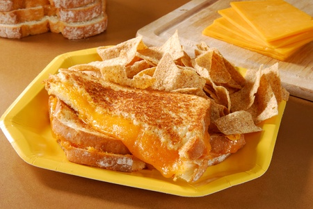 toasted: A grilled cheese sandwich on a yellow paper plate Stock Photo