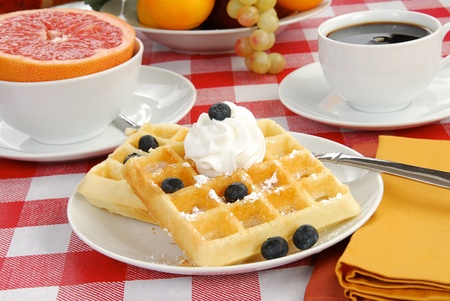 Golden waffles with blueberries and powdered sugar