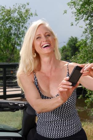 휴가 동안 휴대 전화로 그녀의 사진을 찍는 행복한 여자, 또는 그녀가 방금 읽은 메시지를 통해 흥분한