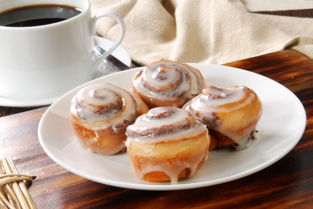 A plate of mini cinnamon rolls and a cup of black coffee photo