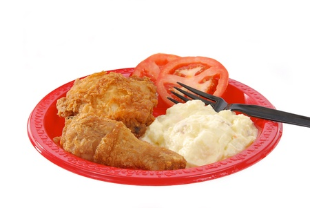 A picnic plate of fried chicken and potto salad on a white background