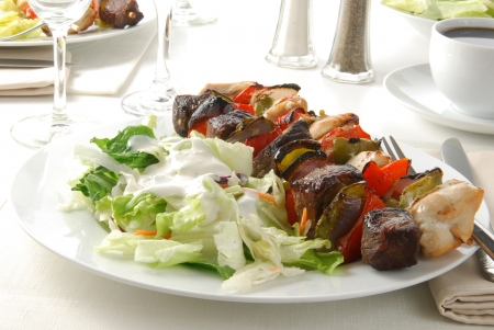 A plate of chicken and beef kebabs and salad photo