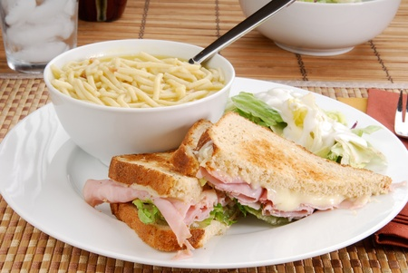 A ham and cheese sandwich with salad and soup