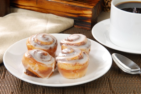 cup four: A plate with four cinnamon rolls and a cup of coffee Stock Photo