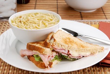 チキン ヌードル スープとハム & チーズ サンドイッチ