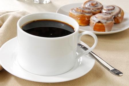 bollos: Una taza de caf� negro y rollos de canela en el desayuno Foto de archivo