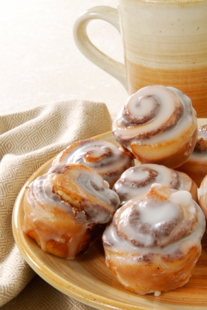 A plate of mini cinnamon rolls with a cup of coffee