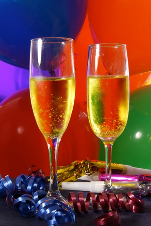 Two flutes of champagne in a party setting with balloons and streamers Imagens