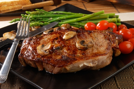 A juicy steak with sauteed mushrooms, cherry tomatoes and asparagus Standard-Bild