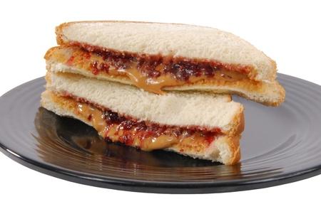 Een pindakaas en aardbeienjam broodje in tweeën gesneden