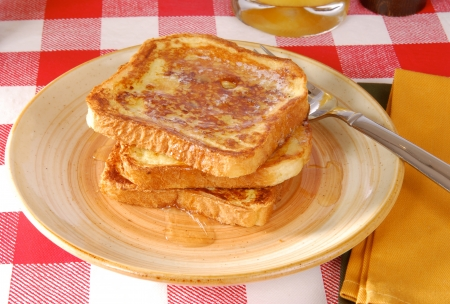 toast: A plate of golden brown french toast with syrup