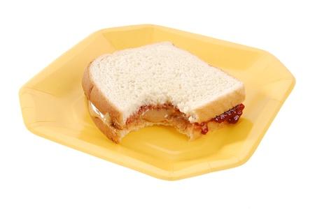 een natuurlijke pindakaas en jam sandwich op een papieren bord Stockfoto