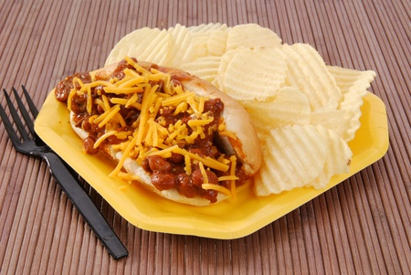 A hot dog smoothered in chili and cheese with chips photo