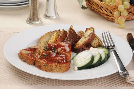 Meatloaf with sliced fried potatoes and cucumbers