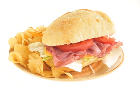 A roast beef submarine sandwich with potato chips photo
