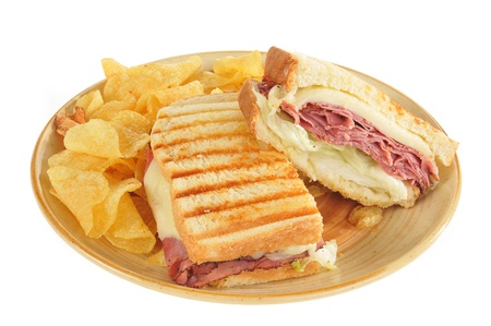A grilled roast beef and swiss cheese panini with potato chips on a white background photo
