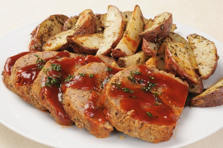 A serving platter of sliced meatloaf and sliced potatoes  Stock Photo