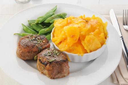 A dinner plate of pork tenderloin and au gratin potatoes