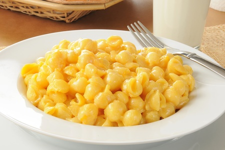 macaroni and cheese: A close up of abowl of macaroni and cheese with a glass of milk