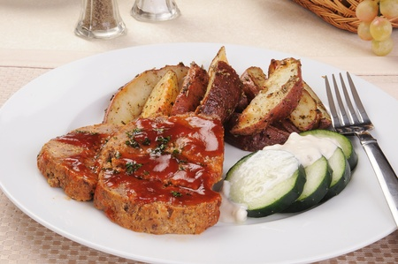A plate of meatloaf, sliced potatoes and cucumbers photo