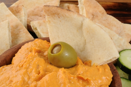 Closeup of red pepper hummus with pita bread and a green olive Stock Photo