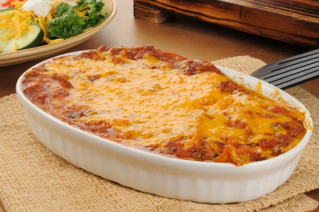 A chicken enchillada casserole topped with cheddar cheese Stock Photo