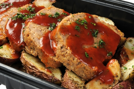 A deli container of sliced meatloaf and potatoes