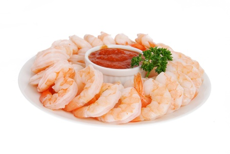 A plate of shrimp prawns with cocktail sauce on a whte background