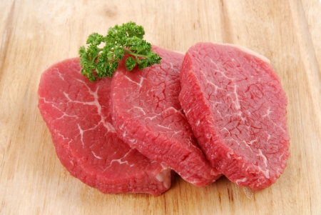 Uncooked beef steaks on a cutting board with garnish Stock Photo - 13604458