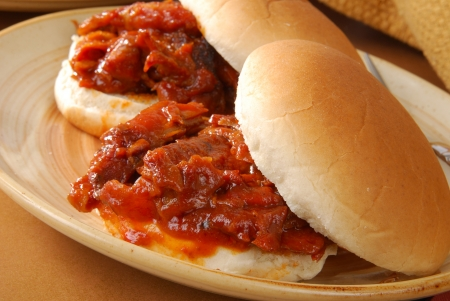 heaping: Close up photo of two barbeque beef sandwiches - shallow dof, focus on front sandwich