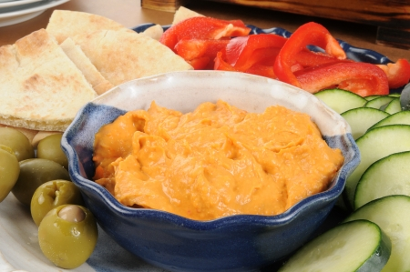 A snack platter of hummus with sliced vegetables and pita bread