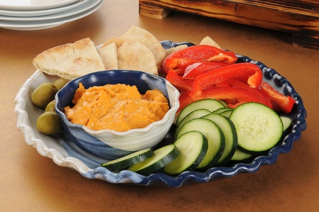 A party tray with hummus, red peppers, pita wedges and green olives Stock Photo