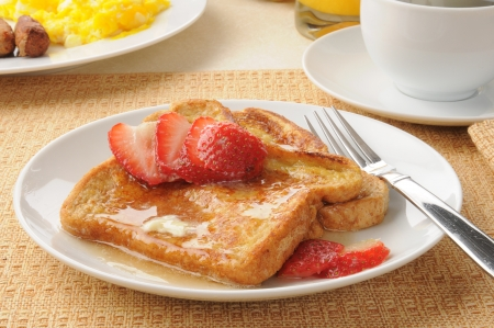 French toast with strawberries with a sausage and egg breakfast photo