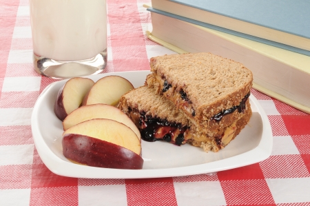 Peanut butter and jelly sandwich with an apple and school text books photo