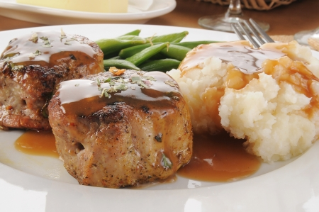 smothered: Pork tenderloin medallions smothered in gravy close up