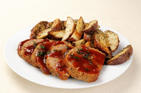 A platter of sliced meatloaf with sliced potatoes photo