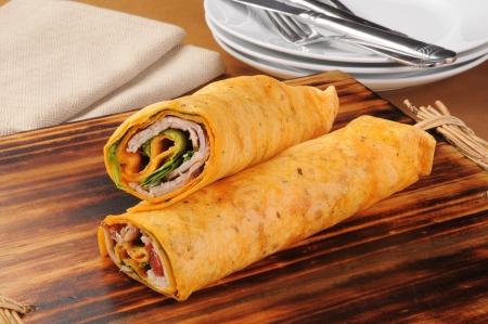 Fresh turkey or chicken wraps with pesto on a chopping board