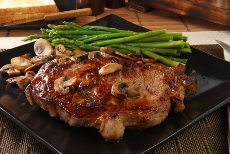 A juicy broiled steak with sauteed mushrooms and asparagus