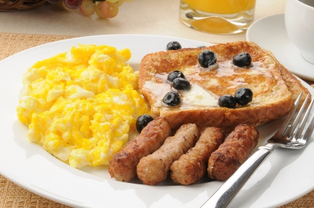 A sausage and egg breakfast with french toast and blueberries