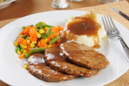 A plate of salisbury steak with mashed potatoes and mixed vegetables