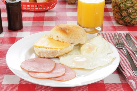 Canadian bacon and fried eggs with a biscuit photo
