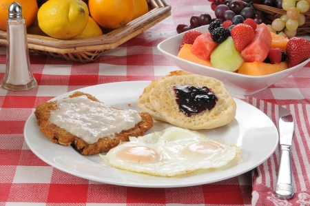 A country fried steak and egg breakfast with fruit salad photo